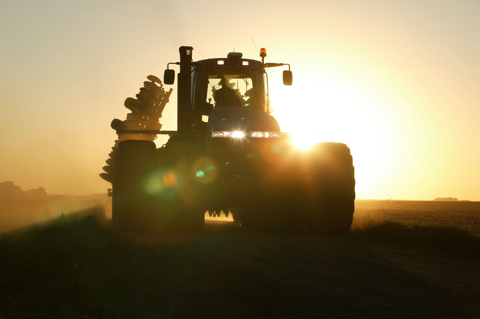 4wd Tractor Driving Through Fields at Sunrise